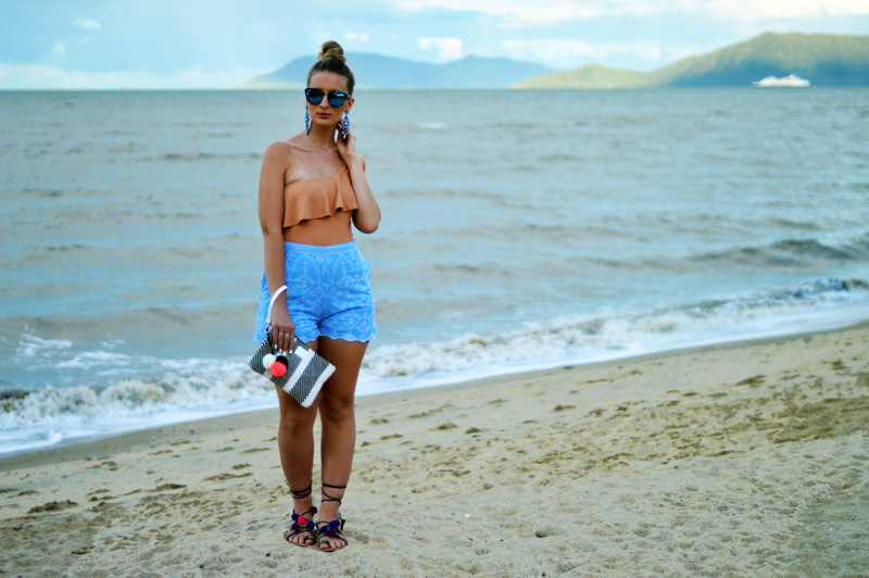 girl on beach wearing one shoulder frill top embroidered shorts pom pom shoes