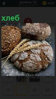 На столе лежат батоны хлеба и выращенные колосья из которых он сделан