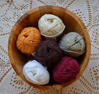 Top view of wool skeins in a round wooden bowl on a filet crochet doily. The skeins are off-white, beige, cream, orange, plum and dark brown.