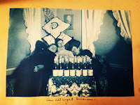 Three guys asleep leaning on each other with champagne bottles lined in front of them
