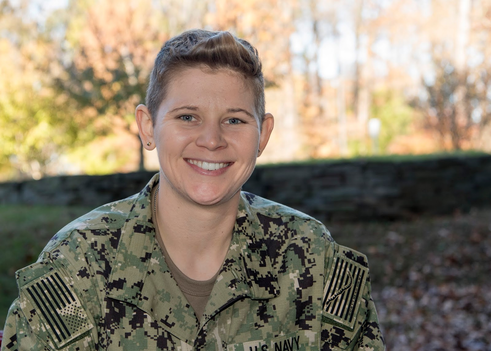 A female in a U.S. Navy uniform poses for a photo outside in front of the woods.