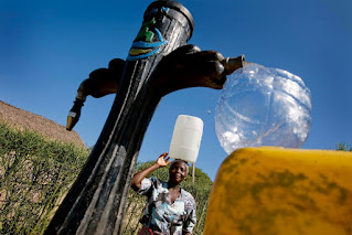 Woman collects water in Costa del Sol near Maputo, Mozambique