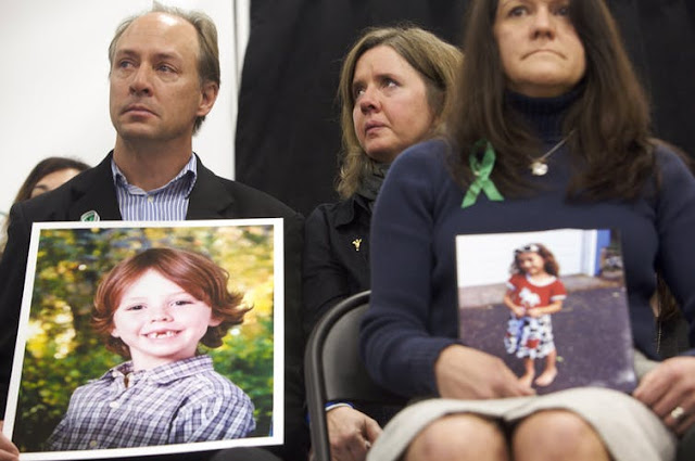 Mark Barden and Jennifer Hensel hold photos of their respective children Daniel Barden, 6, and Avielle Richman, 6, both victims of the Sandy Hook shooting.