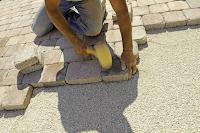 Stratenmaker aan het werk om de straat dicht te leggen, op zijn knieën en een stapel stenen naast zich.
