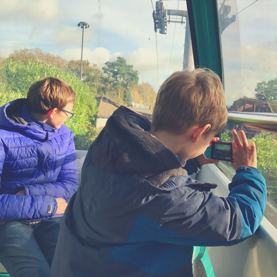 Two boys, teen and a tween, look out of a window. One boy is taking a photo with a camera, they are both looking away from the camera.