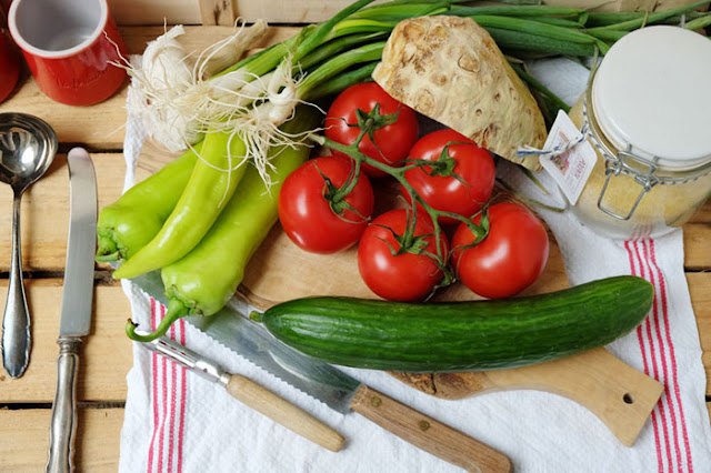 Grüne Paprika, Toaten, Gurke, Sellerie, rote Tomaten auf einem Oliven-Holzbrett mit Messern
