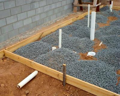 Preparação para concretagem da laje de fundação: instalações hidrossanitárias envoltas de pedras contornadas por tabeira de madeira.
