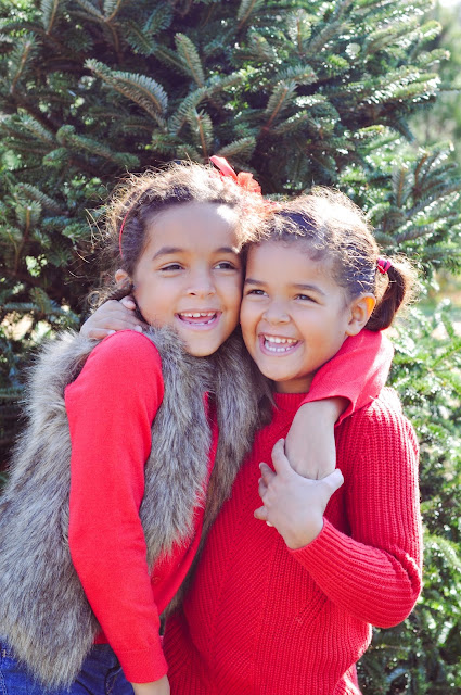 Sisters hugging at a Christmas Tree Farm