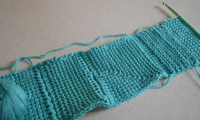 A long sample of tricot fabric with different stitches. A double-ended hook lies on the right hand side, the ball of cotton on the left on top of the test swatch.