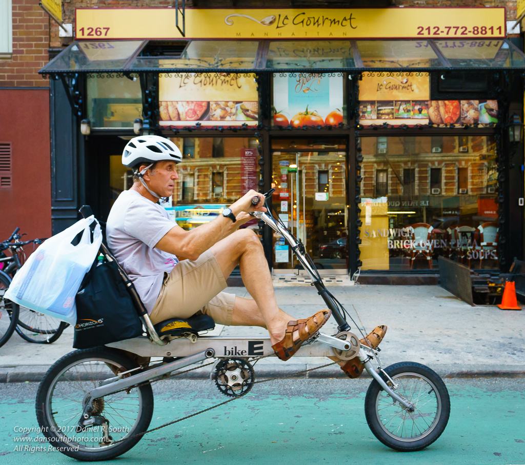 a photo of a man doing shopping errands on a recumbent bicycle in new york city