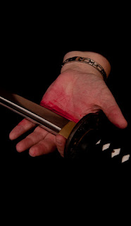 hand holding sword blade, fake blood on palm