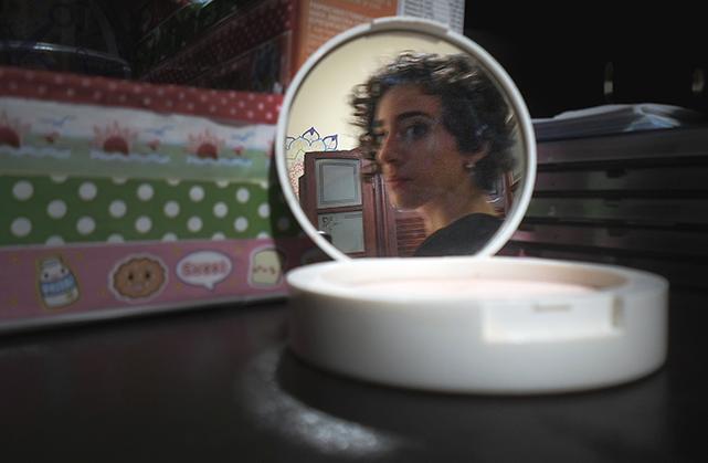 Foto de um estojo de maquiagem em cima de uma prateleira. No espelho é possível ver meu rosto, olhando de lado para o reflexo
