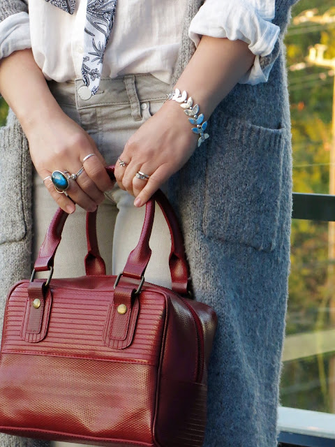 grey skinny jeans, long cardigan, and Elvis & Kresse bag