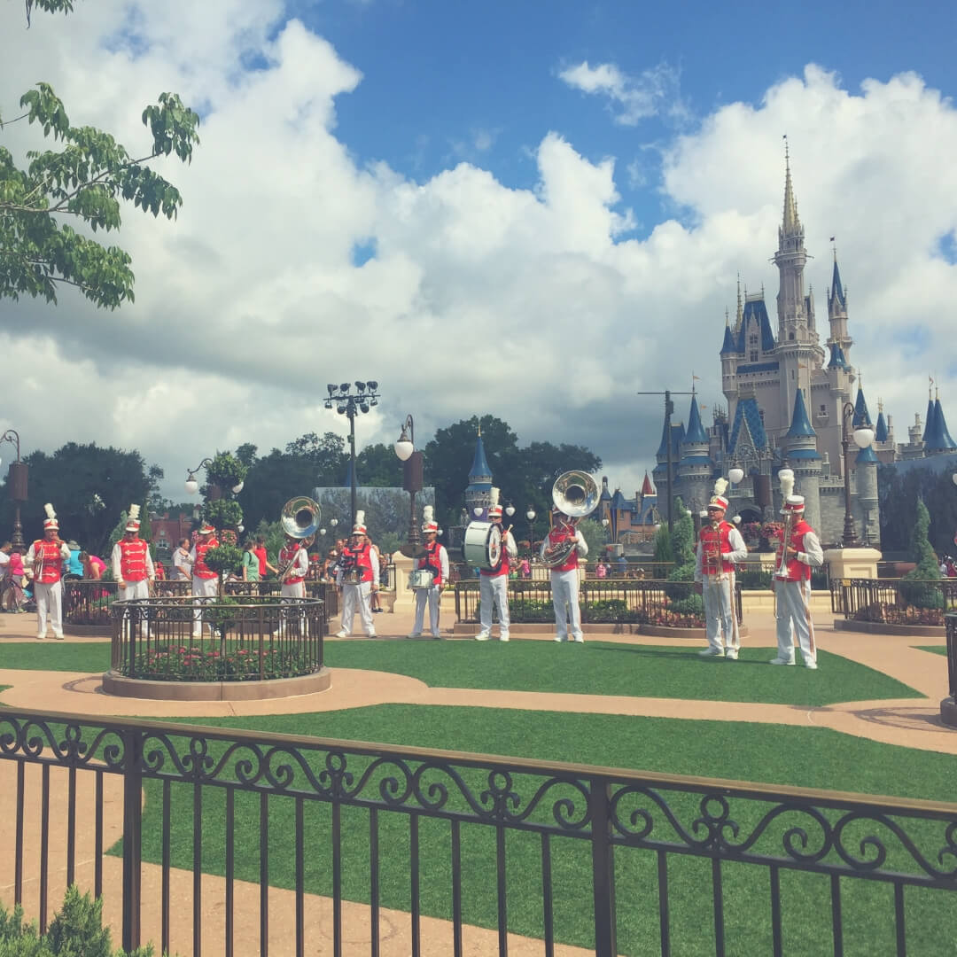 7 Ways To Save Money When In Walt Disney World | A big brass band stands in front of Cinderella's Castle in Magic Kingdom.