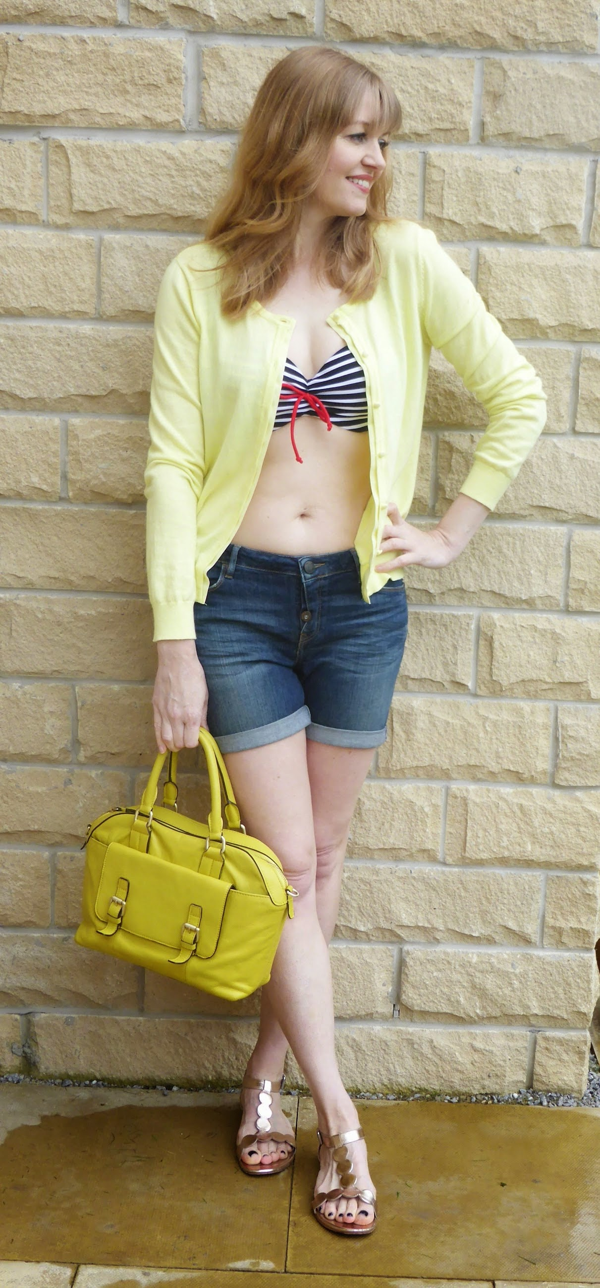 Over 40 fashion blogger What Lizzy Loves wearing navy and white bikini top with denim shorts and lemon yellow cardigan. How to wear a bikini over 40. Bikini for over 40s. Can you wear a bikini over the age of 40. How to wear a bikini when over 40