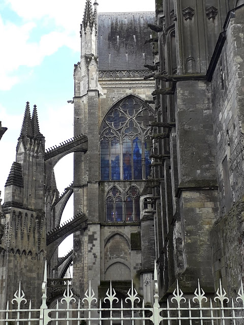 side view of Saint Gatien Cathedral in Tours looking at butress and blue light on stained glass window