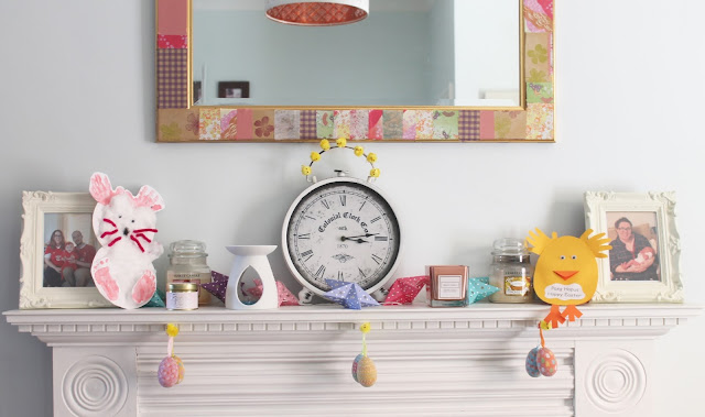 Easter decorated white and pastel fireplace with hanging egg decorations, Easter cards and little chicks