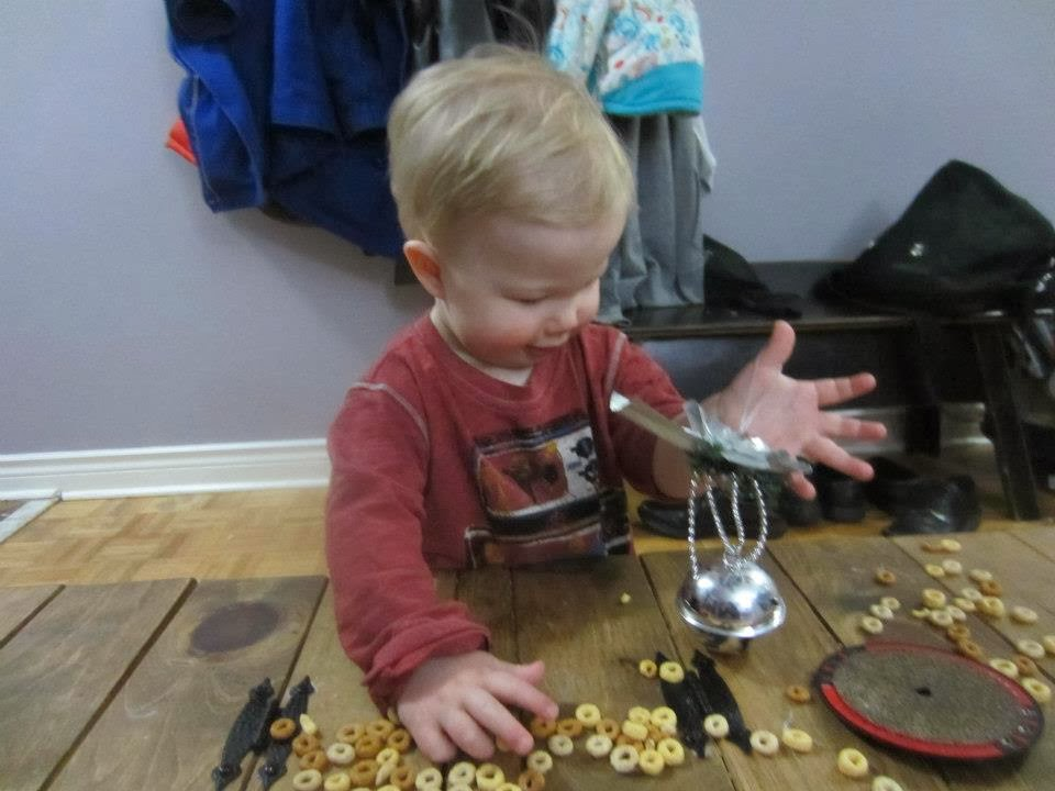 toddler playing with cheerios