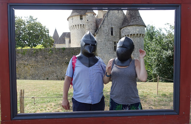 Me and G wearing knights helmets in front of a french chateau