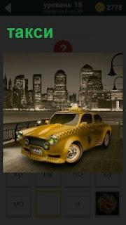 По улицам города едет желтое такси со знаком шашечек на крыше и вдали небоскребы с фонарями