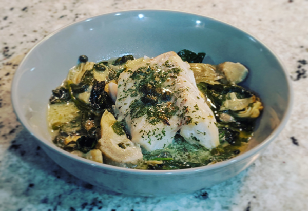 image of cod with spinach, artichokes, and capers in a lemon sauce, in a blue bowl sitting on my kitchen counter