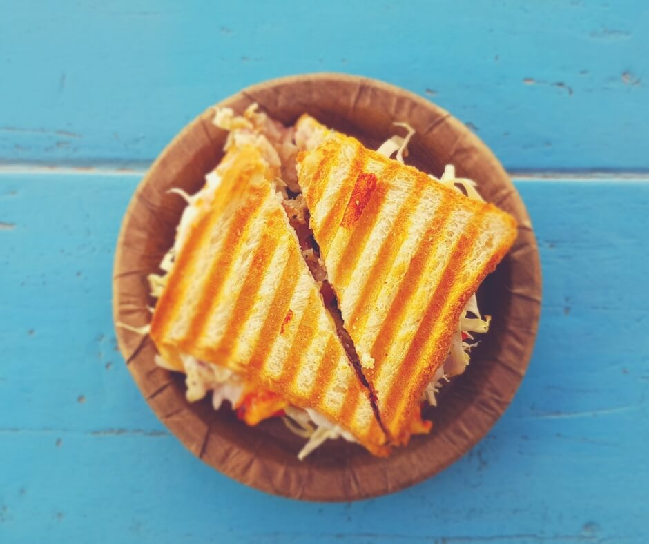 Grilled sandwich on a brown plate on a light blue background.