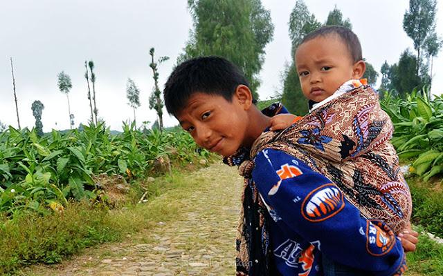 Anak kecil setempat menggendong adikknya