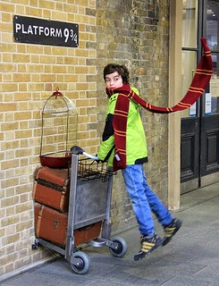 Boy with Gryffindor scarf pushing luggage trolley at platform 9 3/4