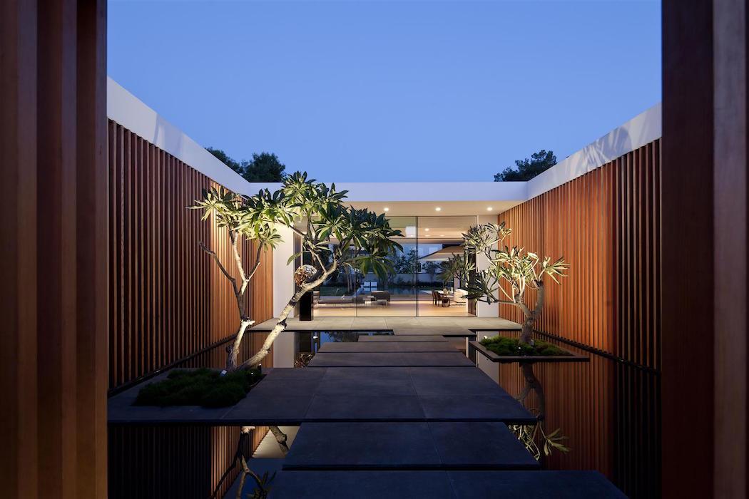 dispone de una piscina con la misma forma del contorno de la vivienda haciendo que la casa se refleje en la superficie del agua como un espejo