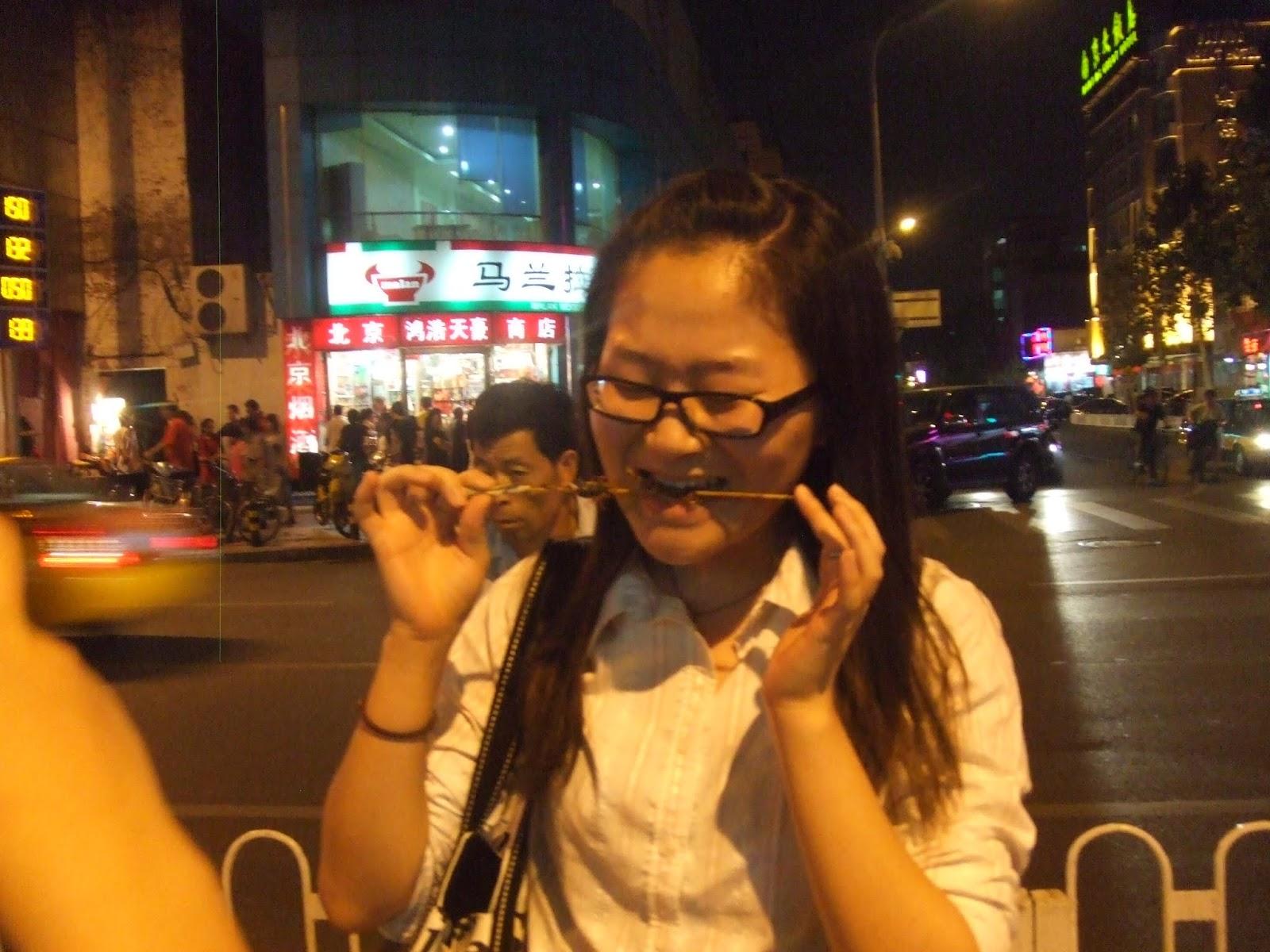 Chinesin isst Skorpion am Abend in der Stadt
