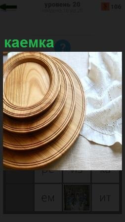 На столе стопкой стоят деревянные тарелки с каемкой от большой к маленькой