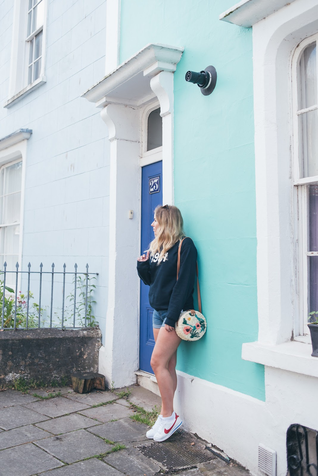 Rachel Emily outside pretty pastel blue houses in Bristol