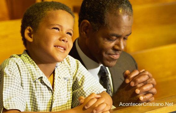 Niño orando con su padre