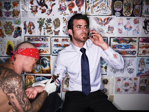 Un hombre de negocios con camisa y corbata tatuandose
