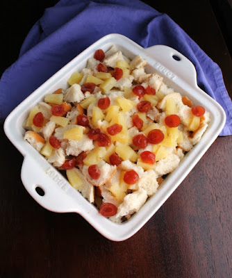 pan with bread cubes, cherries and pineapple chunks in it for tropical bread pudding