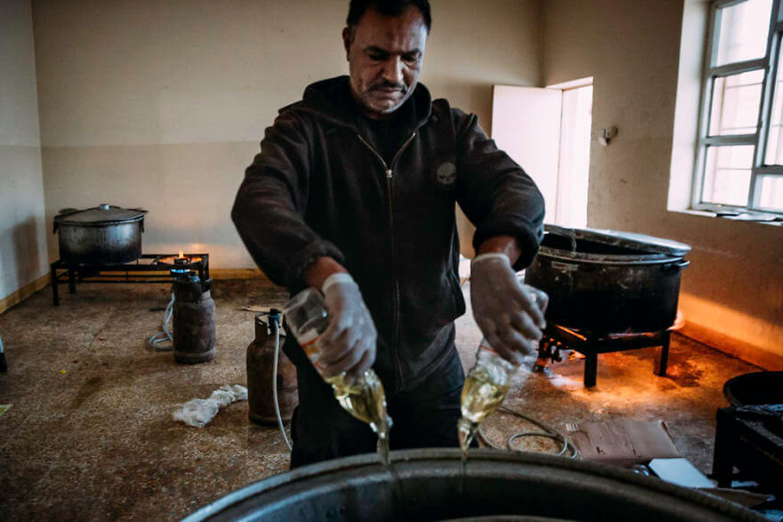 Powerful Heart-Breaking Pictures Of The Battle Of Mosul - A cook prepares large amounts of rice for the soldiers