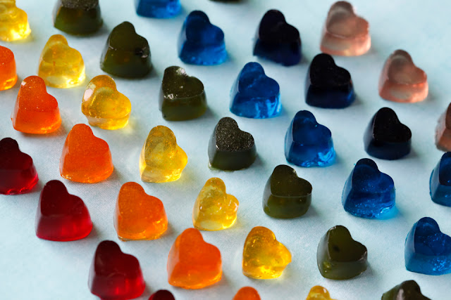 Small homemade gelatin gummy dog treats shaped like hearts arranged in lines as a rainbow of colours