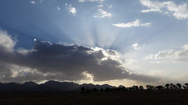 Sol atrás das nuvens com seus raios iluminando