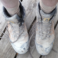 photo looking down at a guys feet standing on a wood deck, wearing very dirty, concrete-dust-covered, work boots with untied laces
