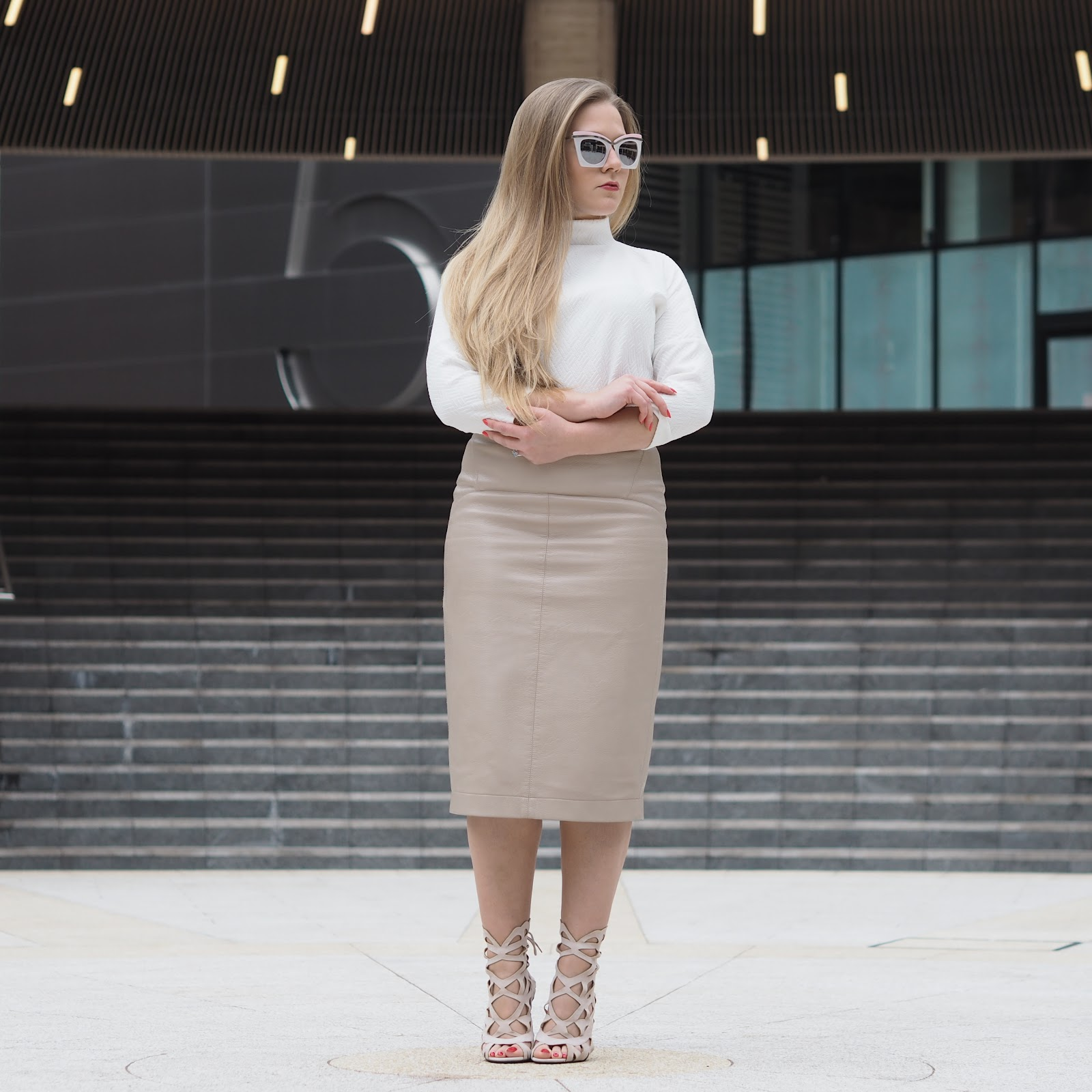 Girl wearing retro sunglasses, white roll neck top, leather skirt and caged, misguided heels