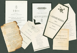 A photograph showing several papers regarding funereal proceedings for mathematics. Some are shaped as coffins or include illustrations of bats and bones.