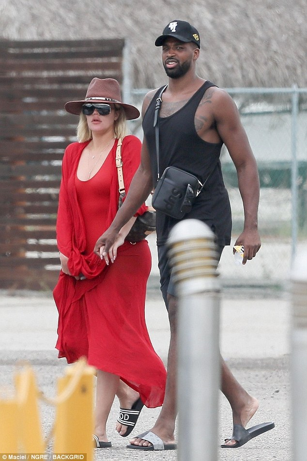 Khloe Kardashian dazzles in red as she holds hands with beau Tristan Thompson during outing in Mexico