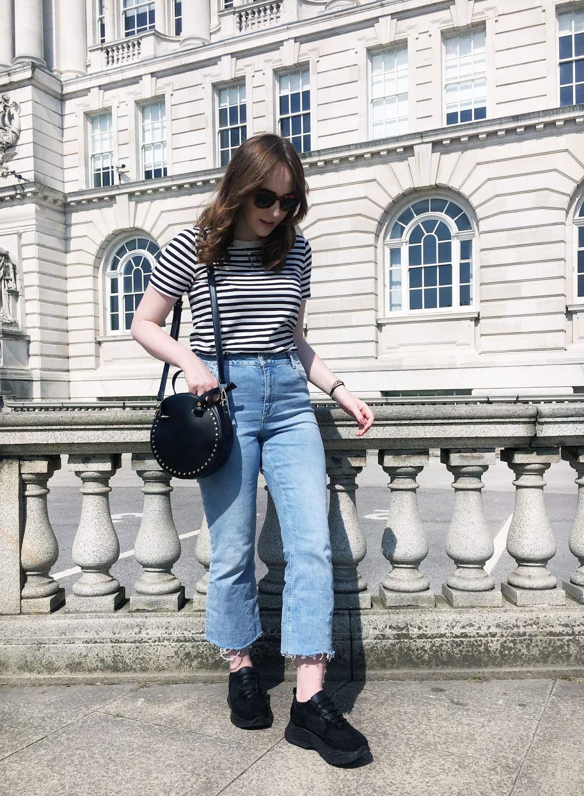 UK style and fashion blogger summer 2018 outfit with light wash blue kick flare jeans, black chunky trainers, black and white stripe t shirt from cos