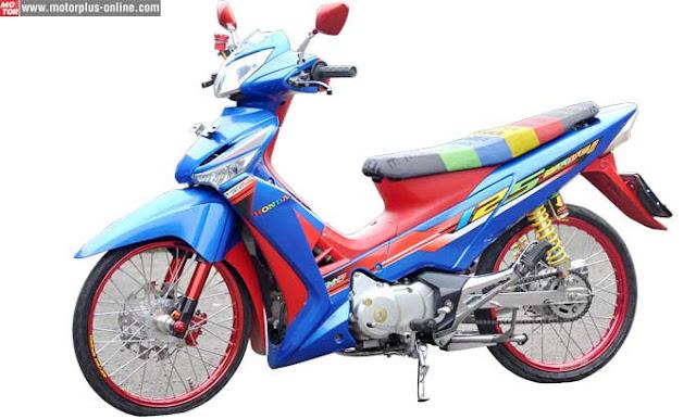 Foto Modifikasi Honda Supra kaki-kaki dan part bolt on Pakai warna cerah, perpaduan biru dan merah stiker Honda Wave 125 turut disematkan. Pemilihan warna jok, terlihat selaras dengan konsep keseluruhan bodi jok Bride kombinasi warna hijau, biru, kuning dan merah