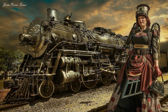 Woman wearing a steampunk train costume-- tracks, wheels, hat, corset, skirt, goggles
