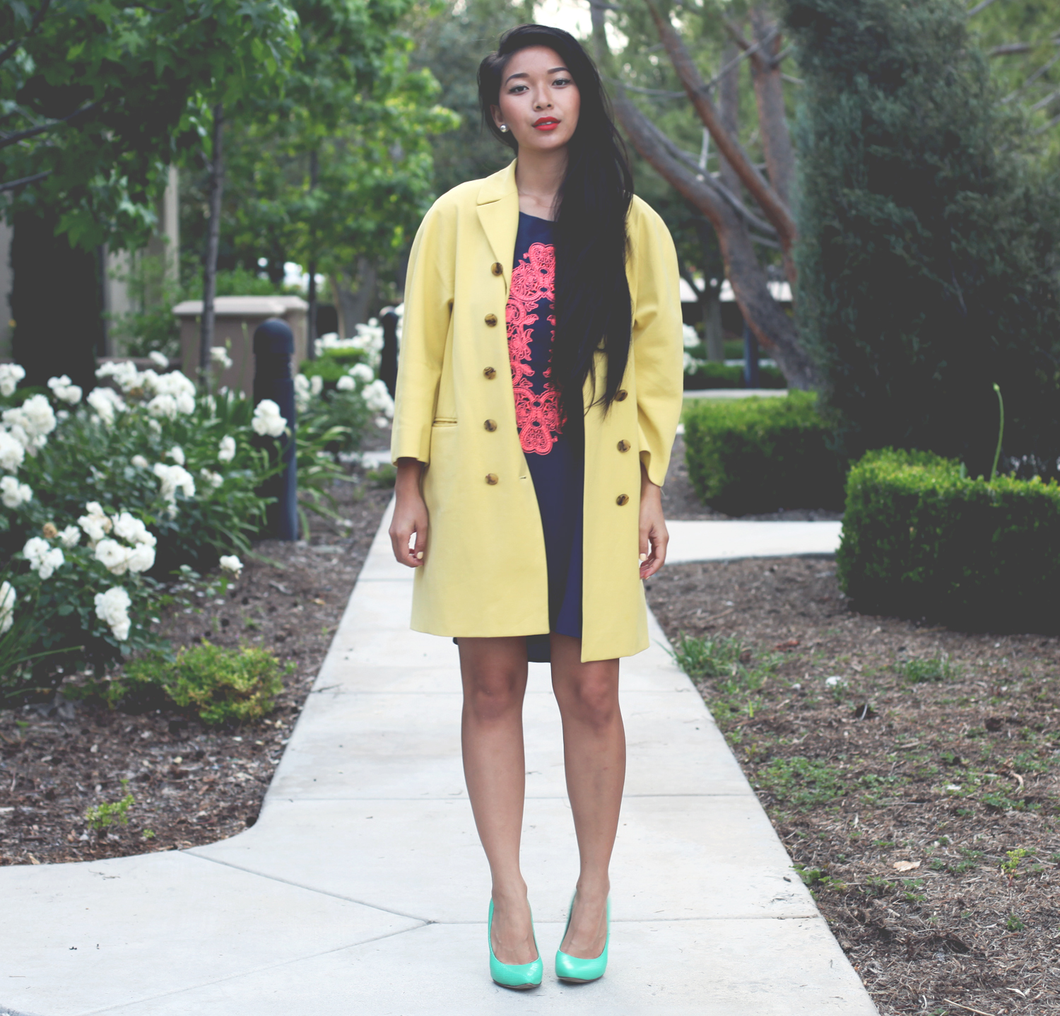 Honey & Silk wearing yellow Jill Stuart coat, Sugarlips filigree dress, and Cole Haan Chelsea Pumps