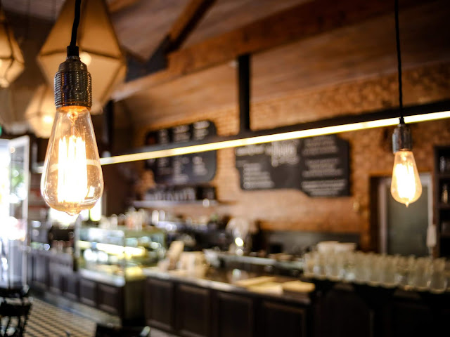 Two bare light bulbs hanging in empty restaurant or cafe