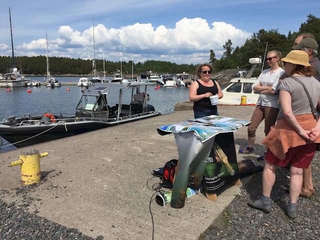 Henkilö esittelemässä postereita ja Metsähallituksen venettä satamassa muutamalle ihmiselle