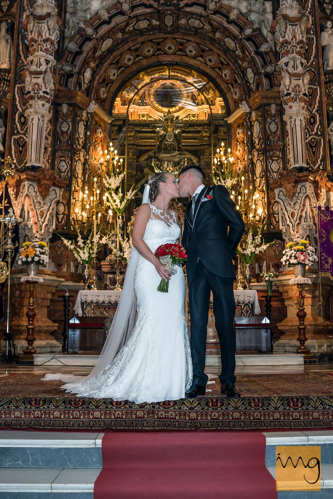 Fotografía de los novios dándose un beso en el altar
