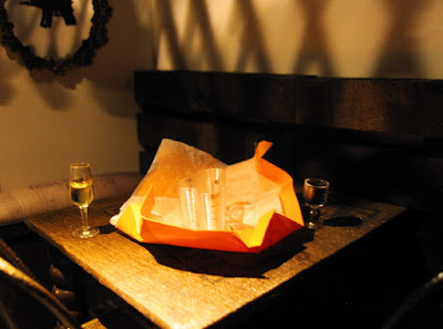 Modern one-twelfth scale miniature scene with two glasses of wine on a table and an unwrapped present between them.